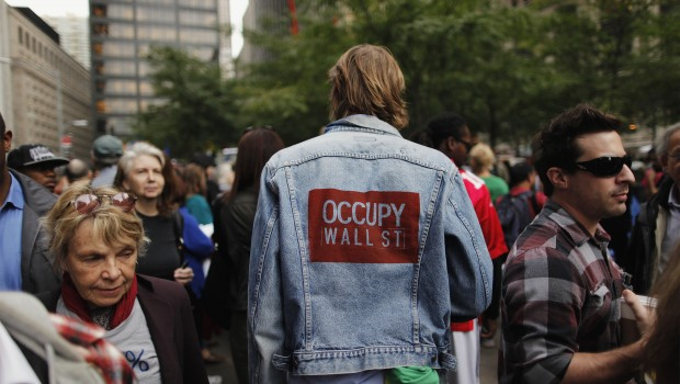 A member of the Occupy Wall Street movement walks among the crowd in Zuccotti Park near the financial district of New York